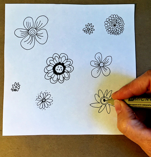 """2. Cut your paper into a 6"""" x 6"""" (15cm x 15cm) square and draw several flowers, careful not to let any of them touch the edges of your square."""