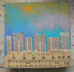 Choose a different paper to lay down for the landscape in the foreground. I used an old music sheet, but it can be anything. Glue everything down with Mod Podge or acrylic medium. (You can use regular craft glue, but thin it down with water in a separate cup until it flows.) Let the piece dry.